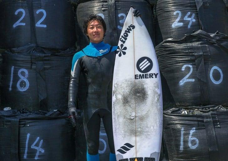 Surfista japonés delante de los sacos de arena contaminados